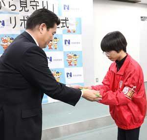奈良県警が作成した「ながら見守り」リボンを大学生防犯ボランティアに贈呈。